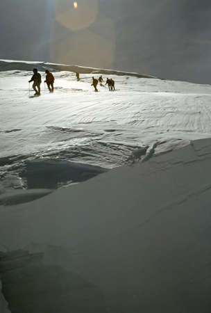 crevasse: Climbers on bergshrund, crevasse on Emmons Glacier,[ lens flare in bright sunlight]  Mt Rainer, Washington