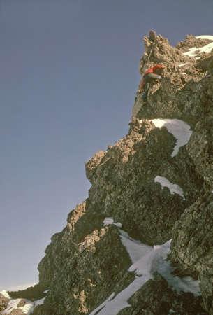 Climber nearing summit of volcanic spire,   Canadian Rockies, winter Alberta, Canada  photo