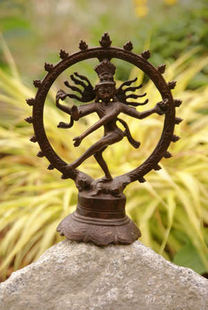 Bronze Shiva in garden, with blades of grass.     Nataraja (Sanskrit: Lord of Dance) Shiva represents apocalypse and creation as he dances away the illusory world of Maya transforming it into power and enlightenment.   Stock Photo