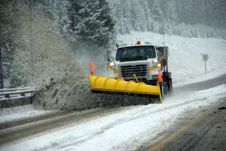 Snowplow clearing road in snowstorm,  Rocky Mountains, Idaho