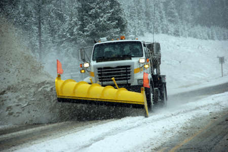 Snowplow clearing road in snowstorm,Rocky Mountains,Idaho Stock Photo - 11511539