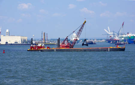 Tugboat pushing dredging barge in New York Harbor, from Staten Island Ferry,    photo