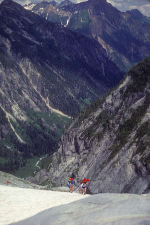 Climbers with full packs descending glacier,  Mt. Challenger North Cascades National Park,  Washington