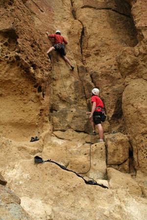 Potholes, climbers on rock face,  Smith Rock State Park,  Central Oregon   Stock Photo