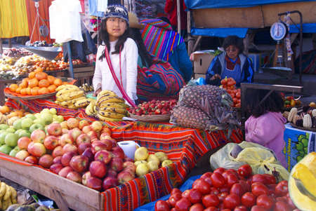 Indian girl selling vegetables, Pisac market,  Cusco, Peru, South America Editorial