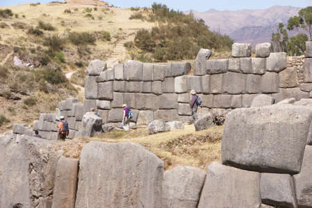 close fitting: Tourists walking past massive stones in Inca fortress walls,  Sacsayhuaman,  Cusco, Peru, South America