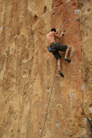 belay: Bare back climber clinging to rock face,  Smith Rock State Park,  Central Oregon  Stock Photo