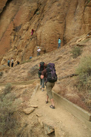 Climbers approaching rock face with backpacks,Smith Rock State Park, Central Oregon Stock Photo - 11614124