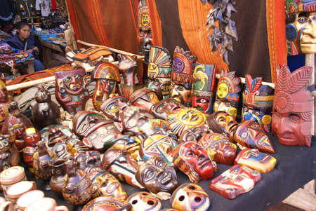 quechua indian: CUSCO, PERU 24 AUGUST 2008 -  Young woman selling painted Inca masks at Pisac Sunday Market near Cusco Peru.