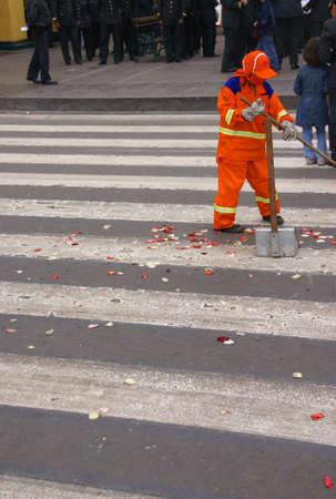 Orange maintenance man, sweeping street after parade,  Lima, Peru, South America photo