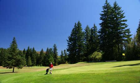 oregon cascades: Red shirted golfer on green,  golf course, Oregon cascades  Stock Photo