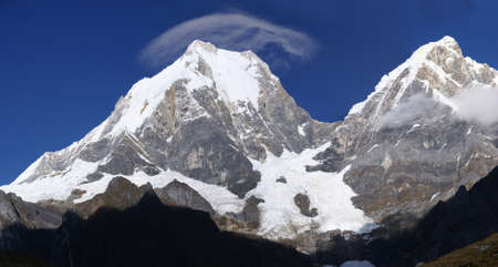 lenticular: Panorama - Jirishanca and Yerupaja mountains in high Andes,  with cloud cap forming as lenticular cloud,  Cordillera Huayhuash, Andes, Peru, South America Stock Photo