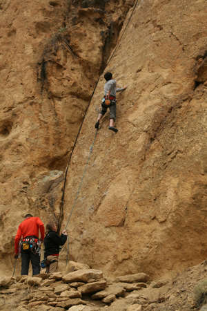 belaying: Woman belaying a climber on rock face,  Smith Rock State Park,  Central Oregon  Editorial