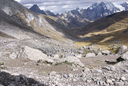erratic: Storm clouds gather over broad glacial valley with erratic granite boulders in the  Cordillera Huayhuash, Andes, Peru, South America