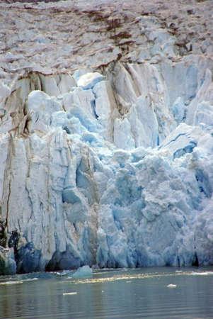 Glacier dropping into ocean, Sawyer Glacier, Endicott Arm Fjord, Alaska Фото со стока