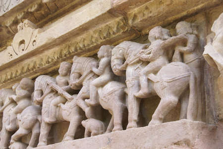 Soldiers of the king on parade, carvings on Lakshmana Temple at Khajuraho in India, Asia  Stock Photo