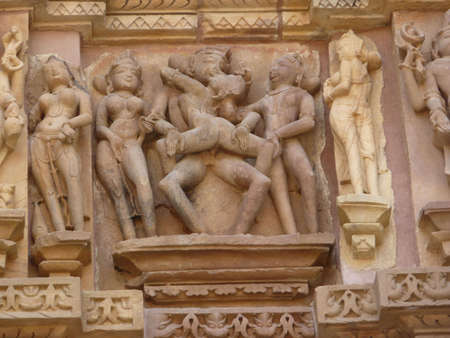 sutra: Sculptures of loving couples, illustrating the Kama Sutra, on walls of  Kandariya Mahadeva Temple at  Khajuraho in  India, Asia