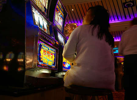 Lone woman playing video slot machines,Cruise ship casino,Pacific Northwest
