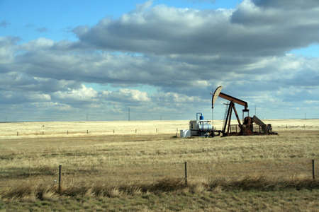 Oil well,on open prairies, with big blue sky Alberta,Canada   Stock Photo