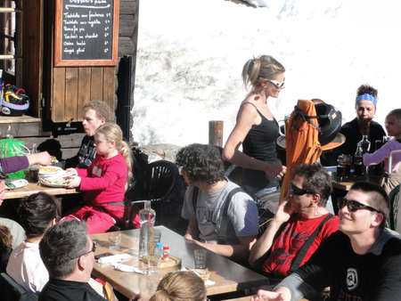 PORTES DU SOLEIL, FRANCE - Mar 3 - A pretty blonde waitress serves lunch outdoors on Mar 3, 2012, at the Portes du Soleil, France.