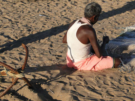 india fisherman: A fisherman repairs his nets in Puri, India  Editorial