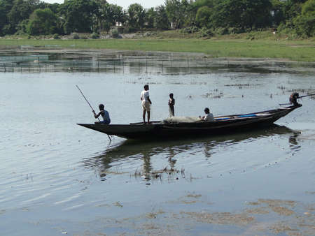 Fishermen silhouetted in their long boat  in a salt marsh in Puri, India