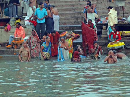 woman bath: VARANASI, INDIA - NOV 6 -  Hindus perform ritual puja at dawn in the Ganges River  on Nov 6, 2009,  in Varanasi, India.