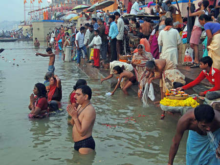 bathing man: VARANASI, INDIA - NOV 6 -  Hindus perform ritual puja at dawn in the Ganges River  on Nov 6, 2009,  in Varanasi, India.