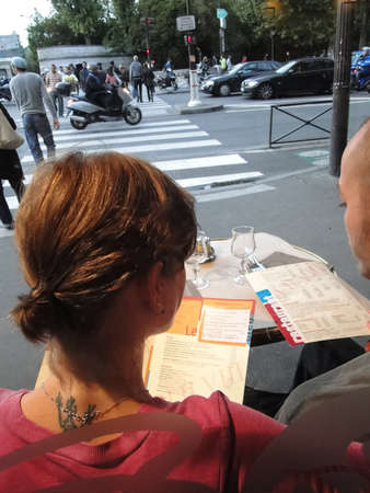 atilde: PARIS - SEP 11 - Young couple watches evening traffic from his seat in an outdoor bistro  on Sep 11, 2011, in Paris, France...