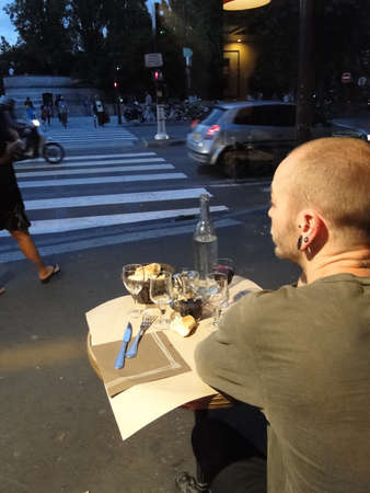 PARIS - SEP 11 - Young man watches evening traffic from his seat in an outdoor bistro  on Sep 11, 2011, in Paris, France... Stock Photo - 13511821