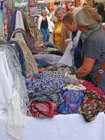 VAISON LA ROMAINE, FRANCE - SEP 27 - A woman shops for a  colorful scarf  at the weekly market,  on Sep 27, 2011 in Vaison la Romaine, France.