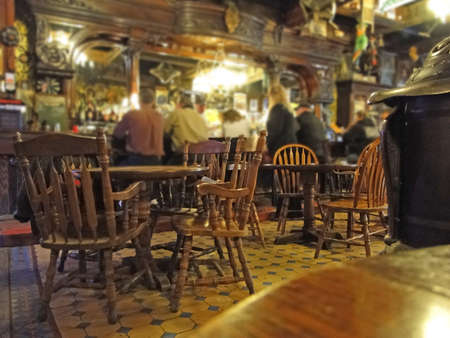 Patrons sit at the old western bar in a tavern in Leadville, CO