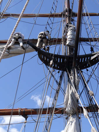 Crew unfurls a sail on a yardarm of a tallship  near Kirkland, Washington   Stock fotó