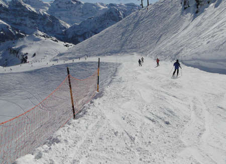 Snow fence lines the piste  on a steep descent in the Portes du Soleil, Switzerland