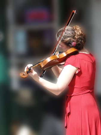 violins: SEATTLE - MAY 15 -  Female violinist entertains the crowd  at the U District Street Fair on May 15, 2010, in Seattle   Editorial