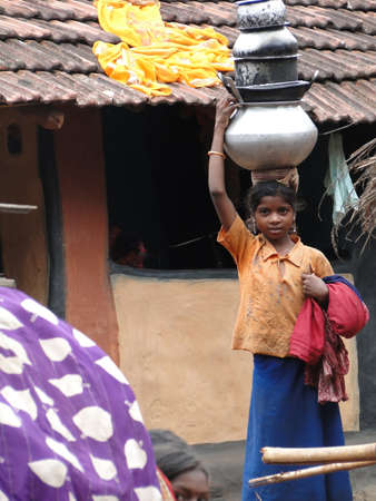ORISSA,  INDIA - NOV 12  - Young girls learn to carry water pots on their heads  on Nov 12, 2009 in Orissa, India..