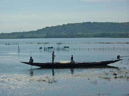 Fishermen silhouetted in their long boat  in a salt marsh in Puri, India  Stock Photo