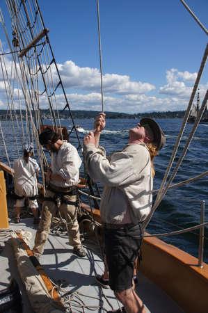 chieftain: KIRKLAND, WASHINGTON - AUG 31 - The crew rigs the sails of the Hawaiian Chieftain as she sails on Lake Washington    during a mock sea battle as part of Labor Day festivities on Aug 31, 2012 near Kirkland , Washington.   Editorial