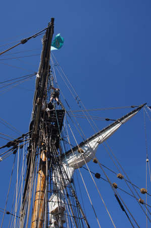 Sailor climbs the rigging  on the mast of a tall ship