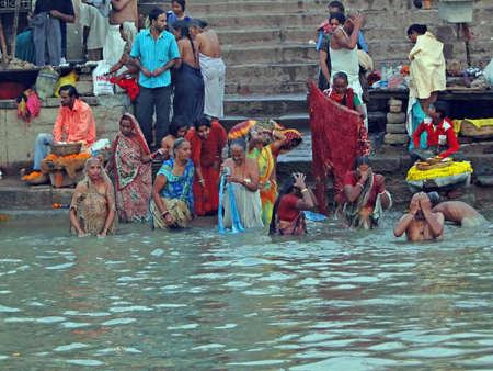 ghat: VARANASI, INDIA - NOV 6 -  Hindus perform ritual puja at dawn in the Ganges River  on Nov 6, 2009,  in Varanasi, India.