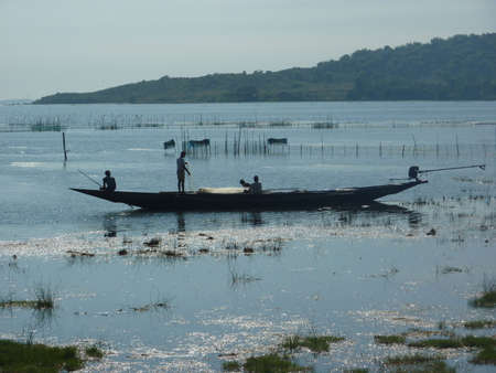 puri: Fishermen silhouetted in their long boat  in a salt marsh in Puri, India  Stock Photo