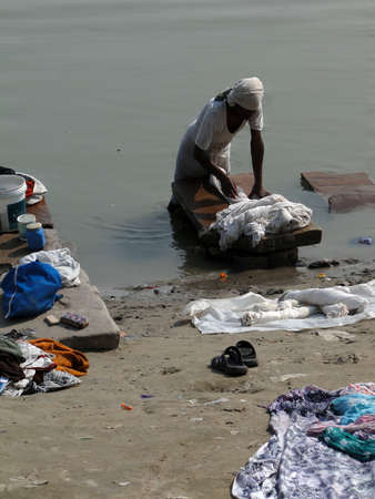 dhobi ghat: VARANASI, INDIA - NOV 7 - Dhobiwallah washes clothes in the Ganges River on Nov 7, 2009, in Varanasi, India.