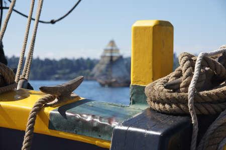 bulwark: Bulwark and coiled rope with tall ship sailing in background  near Kirkland , Washington.