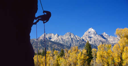 abseil: Climber on rappel, silhouette,fall colors of Grand Tetons National Park,    Stock Photo