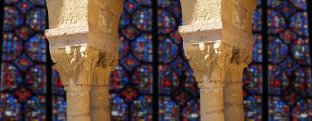 Carved Corinthian capitals from a medieval cloister with background of stained glass, France photo