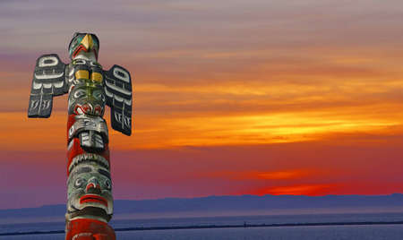 strait of juan de fuca: Thunderbird totem pole with sunset on San Juan de Fuca Strait   Sequim, WA, Peninsula
