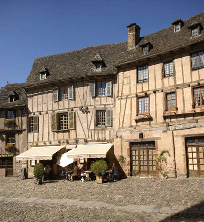 CONQUES, FRANCE -   Midday diners eat under the awning of a half-timbered house  in Conques, France
