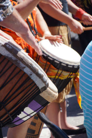 drumming: Close up of drumming by woman in bright clothes, Penticton, British Columbia, Canada..   Stock Photo