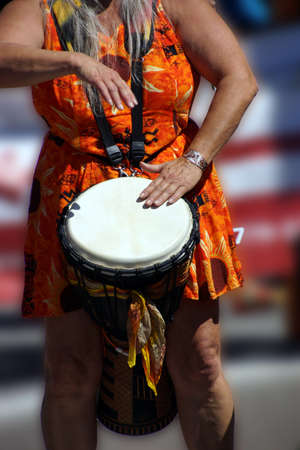 Close up of drumming by woman in bright clothes, Penticton, British Columbia, Canada..