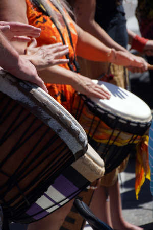 drumming: Close up of drumming by woman in bright clothes, Penticton, British Columbia, Canada..